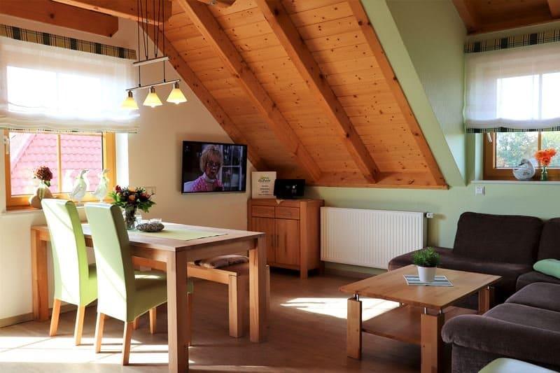 Wohnzimmer mit Esstisch und TV Ferienwohnung Rosmarin