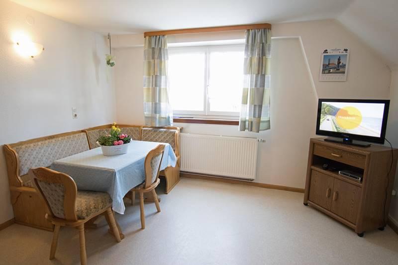Wohnecke mit Esstisch und TV in der Ferienwohnung 2
